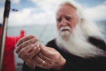 Primo piano del pescatore regolazione amo da pesca sulla barca da pesca — Foto stock