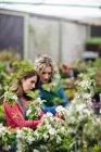 Deux fleuristes femelles à l'aide de tablette numérique tout en vérifiant les plantes en jardinerie — Photo de stock