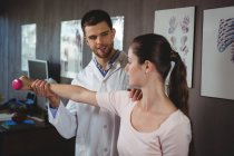 Физиотерапевт корректирует положение пациентки в клинике — стоковое фото