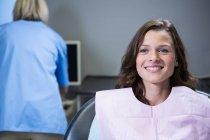 Paziente sorridente seduto sulla sedia del dentista in clinica — Foto stock
