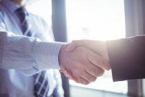 Обрезанный образ бизнесмена, пожимающего руку коллеге в офисе — стоковое фото