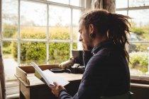 Hipster uomo lettura libro per finestra a casa — Foto stock
