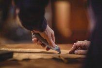 Mãos de sapateiro cortando um pedaço de couro na oficina — Fotografia de Stock