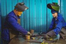 Чоловічі і жіночі зварювальники, які працюють разом в майстерні — стокове фото