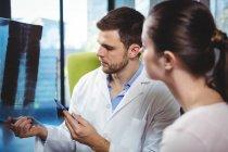 Физиотерапевт объясняет рентген позвоночника пациентке в клинике — стоковое фото