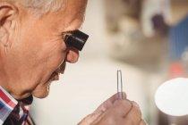 Goldschmied untersucht Diamanten durch Lupe in Werkstatt — Stockfoto