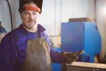 Welder standing with welding machine in workshop — Stock Photo