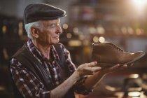 Старший сапожник в кепке осматривает обувь в мастерской — стоковое фото