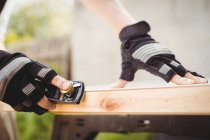 Zugeschnittenes Bild eines Zimmermanns, der Meißel auf Stein schärft — Stockfoto