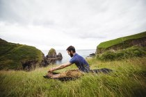 Hombre realizando yoga en acantilado - foto de stock