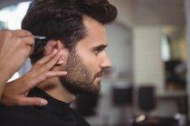 Cabeleireiro aparar o cabelo do cliente no salão de cabeleireiro — Fotografia de Stock