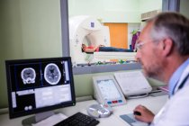 Médico examinando resonancia magnética cerebral en computadora en el hospital - foto de stock