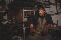 Portrait of blacksmith in protective helmet at work shop — Stock Photo