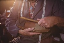 Mid section of shoemaker hammering on a shoe in workshop — Stock Photo
