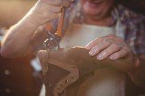 Seção média de sapateiro reparando um sapato na oficina — Fotografia de Stock