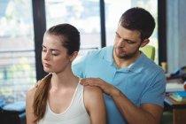 Fisioterapeuta masajeando hombro de paciente femenina en clínica - foto de stock