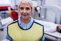 Портрет улыбающегося врача, стоящего в рентгеновской палате в больнице — стоковое фото