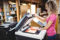 Woman using copy machine in library — Stock Photo