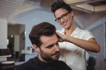 Cabeleireiro aparar cliente o cabelo no salão de cabeleireiro — Fotografia de Stock