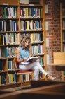 Frau sitzt und liest Buch in Bibliothek — Stockfoto