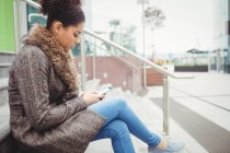 Side view of woman using phone while sitting on steps — Stock Photo