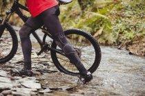 Низкий участок горных велосипедистов, пересекающих реку в лесу — стоковое фото