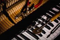Close-up de ferramentas de reparação mantidos no teclado antigo piano na oficina — Fotografia de Stock