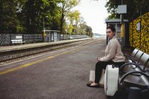 Красива жінка, сидячи на лавці в платформи Залізничні станції — стокове фото