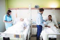 Médicos interactuar con los pacientes en sala de hospital - foto de stock