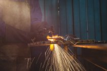 Cropped image of female welder working on piece of metal in workshop — Stock Photo