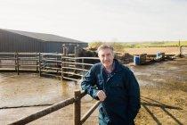 Portrait d'un travailleur agricole penché sur une clôture au champ — Photo de stock