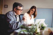 Homem discutindo com colega sobre laptop no escritório — Fotografia de Stock