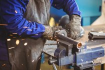 Cropped image of welder sawing metal with electric tool in workshop — Stock Photo
