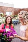 Floristin und Frau betrachten Blume im Gartencenter — Stockfoto