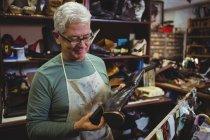 Sapateiro maduro examinando um sapato na oficina — Fotografia de Stock
