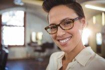 Портрет улыбающейся парикмахерши в салоне — стоковое фото