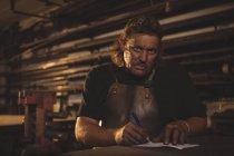 Retrato de ferreiro preparando notas na oficina — Fotografia de Stock