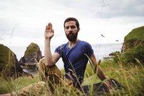 Hombre realizar yoga en acantilado - foto de stock