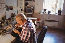 Уважний Голдсміт за допомогою ручної шматок машини в майстерні — стокове фото