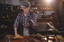 Старший шевця з кришкою, вивчаючи взуття в майстерні — стокове фото