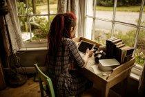 Вид сзади женщины с помощью цифрового планшета за окном дома — стоковое фото