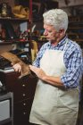 Sapateiro examinando um sapato na oficina — Fotografia de Stock