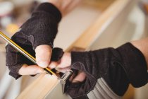 Cropped image of carpenter marking on door with pencil — Stock Photo