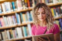 Femme utilisant une tablette numérique dans la bibliothèque — Photo de stock