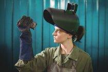 Жіночий зварювальник вивчення шматок металу в майстерні — стокове фото