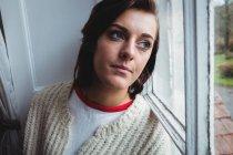 Femme réfléchie regardant par la fenêtre à la maison — Photo de stock
