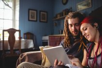 Romantic hipster couple using digital tablet while sitting at home — Stock Photo