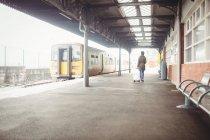 Заднього вигляду жінки, що несе багажу під час прогулянки в платформи Залізничні станції — стокове фото