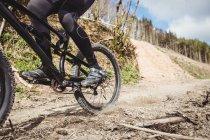 Низкая часть горных велосипедистов едет по грунтовой дороге в горах — стоковое фото