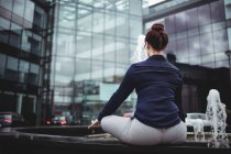 Rear view of businesswoman doing yoga against office building — Stock Photo